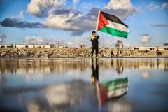 A Palestinian child carrying a flag on the beach Stock Photos