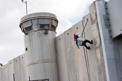 Palestinian climbs Israeli separation wall. BETHLEHEM, OCCUPIED PALESTINIAN TERRITORIES - MARCH 30: A Palestinian scales the Israeli separation wall during Royalty Free Stock Images