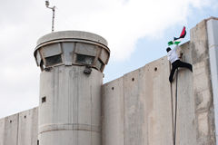 Palestinian climbs Israeli separation wall. BETHLEHEM, OCCUPIED PALESTINIAN TERRITORIES - MARCH 30: A Palestinian scales the Israeli separation wall and plants Stock Photography