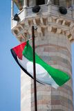 Palestinian flag waving in the wind in front of a minaret stock images