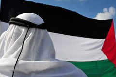 Palestinian Man and Flag. A Palestinian man is wearing a traditional keffiyeh or ghutra (white) and iqal (black) with the Palestinian flag in the background Stock Images