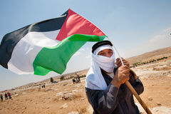Palestinian man with flag in West Bank. SUSYA, OCCUPIED PALESTINIAN TERRITORIES - JUNE 22: An elderly Palestinian man waves a flag in a demonstration near Susya Royalty Free Stock Image
