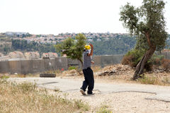 Palestinian Protester Shooting Rock at Protest. Bil'in, Palestine - May 17th, 2013: A Palestinian protester using his slingshot to shoot a rock at the soldiers Stock Images