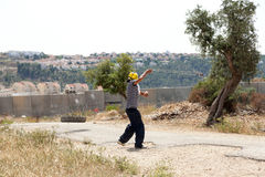 Palestinian Protester Shooting Rock at Protest. Bil'in, Palestine - May 17th, 2013: A Palestinian protester using his slingshot to shoot a rock at the soldiers Royalty Free Stock Photography