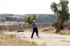Palestinian Protester Shooting Rock at Protest. Bil'in, Palestine - May 17th, 2013: A Palestinian protester using his slingshot to shoot a rock at the soldiers Stock Photos