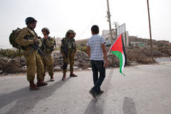 Palestinian Protesters Confront Israeli Soldiers. Al-MASARA, OCCUPIED PALESTINIAN TERRITORIES - OCTOBER 21: Palestinian activists confront Israeli soldiers to Stock Images