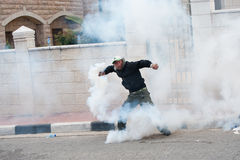 Palestinian throws back tear gas. BETHLEHEM, OCCUPIED PALESTINIAN TERRITORIES - MARCH 30: A Palestinian throws aside a tear gas grenade fired by Israeli soldiers Royalty Free Stock Photography
