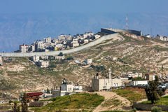 Palestinian town behind separation wall in Israel. Small village and palestinian town on the hill behind israeli separation barrier on the West Bank in Israel Stock Photo