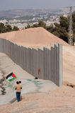 Palestinians and Israeli Separation Barrier. AL-WALAJA, OCCUPIED PALESTINIAN TERRITORIES - NOVEMBER 13: A father and daughter waving a Palestinian flag stand Stock Image