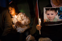 Palestinians and Israelis protest Gaza attacks. A girl holds a candle next to a photo of 3-year-old Ranan Yousef Arafat, who was killed by Israeli airstrikes in stock photos
