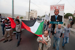 Palestinians and Israelis protest Gaza attacks. Palestinians carrying a flag and Israeli activists with posters of Benjamin Netanyahu with the slogan Denier of royalty free stock image