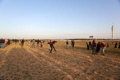 Palestinska personer som protesterar under sammandrabbningar med israeliska styrkor nära denGaza gränsen royaltyfria bilder