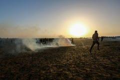Palestinska personer som protesterar under sammandrabbningar med israeliska styrkor nära denGaza gränsen royaltyfri bild