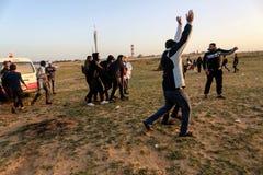 Palestinska personer som protesterar under sammandrabbningar med israeliska styrkor nära denGaza gränsen royaltyfri fotografi