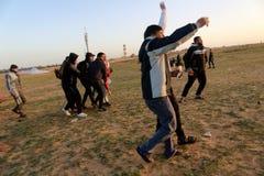 Palestinska personer som protesterar under sammandrabbningar med israeliska styrkor nära denGaza gränsen arkivbilder
