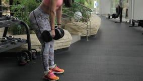 In palestra la donna piega giù con le teste di legno pesanti in sue mani stock footage
