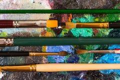 Palet met droge olieverf en reeks borstels royalty-vrije stock afbeeldingen