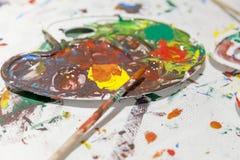 Palet met gemengde kleuren met penselen Stock Afbeelding