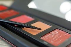 Palet met lipgloss, borstel op de lijst in de schoonheidssalon royalty-vrije stock fotografie