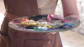 Palet met verschillende kleuren van olieverf in hand kunstenaar stock video