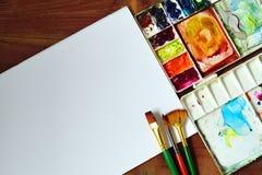 Palet van waterverf met borstel diverse grootte en Witboek op houten textuurachtergrond Royalty-vrije Stock Afbeeldingen