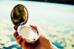 A paleta aberta do pó na mão da fêmea pronta para compõe Fundo borrado bonito fotografia de stock royalty free