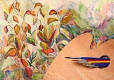 Paleta, brochas y paisaje de la acuarela Imagen de archivo libre de regalías
