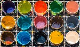 Paleta colorida da pintura, com os doze vidros plásticos que contêm cores diferentes e várias da pintura imagens de stock royalty free