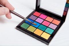 Paleta colorida del primer para el maquillaje con el cepillo de la tenencia de la mano Foto de archivo libre de regalías