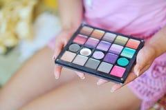 Paleta colorida del sombreador de ojos del maquillaje en manos Foto de archivo libre de regalías