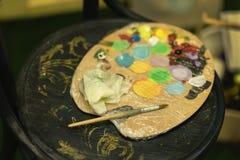 Paleta colorida suja dos artistas no cartão para misturar cores de óleo vibrantes, fundo de madeira escuro Passatempo da arte, ex foto de stock