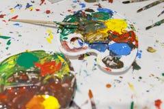 Paleta com cores misturadas com pincéis fotografia de stock