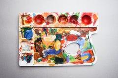 Paleta com pinturas coloridas do artista em um fundo cinzento Fotografia de Stock