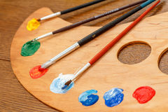 Paleta com pinturas e pincéis Fotografia de Stock Royalty Free