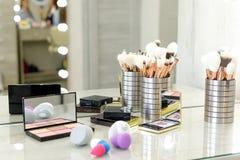 Paleta com sombras, escovas e esponjas na tabela no salão de beleza imagens de stock