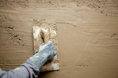 Paleta con la mano del guante que enyesa el mortero del cemento Foto de archivo libre de regalías