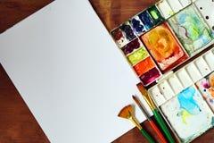 Paleta da aquarela com escova, papel em de madeira Foto de Stock