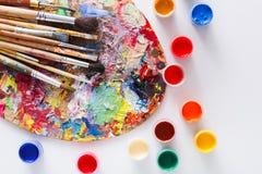 Paleta da arte com os cursos coloridos da pintura, isolados Fotografia de Stock