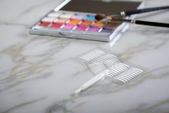 Paleta da sombra para os olhos, escovas e fitas dobro do vinco artificial da pálpebra para a composição do olho na beleza de márm fotos de stock