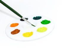 Paleta de colores con el cepillo en la mirada blanca del lado del fondo Imagen de archivo
