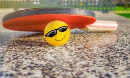 Paleta de la tabla del tenis con una bola sonriente Imagen de archivo libre de regalías