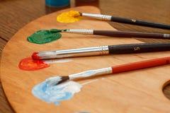 Paleta de madeira com pinturas e pincéis Imagem de Stock