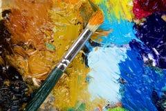 Paleta de madera del arte con gotas de la pintura y de un cepillo en el fondo blanco foto de archivo libre de regalías