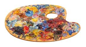 Paleta de madera del arte con las pinturas de aceite y cepillos aislados en whi Foto de archivo