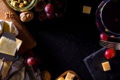 Paleta de muitos tipos de queijo e alguns uvas, azeitonas e vinho Fotografia de Stock Royalty Free