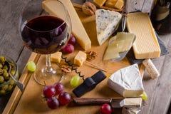 Paleta de muitos tipos de queijo e alguns uvas, azeitonas e vinho Imagem de Stock Royalty Free
