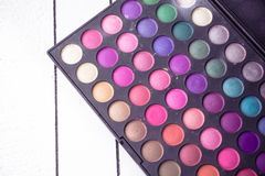Paleta de sombras de ojos coloridas en el fondo blanco de madera Foto de archivo libre de regalías