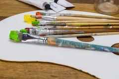 Paleta del arte con los cepillos coloridos del arte con la naranja, amarilla Imagenes de archivo