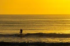 Paleta del hombre que practica surf en la salida del sol foto de archivo