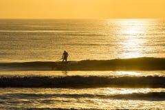 Paleta del hombre que practica surf en la salida del sol imagenes de archivo